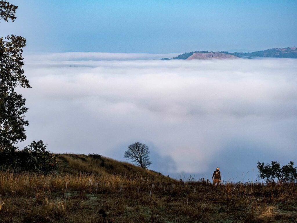A single hunter walks along the hillside of the Oregon uplands.