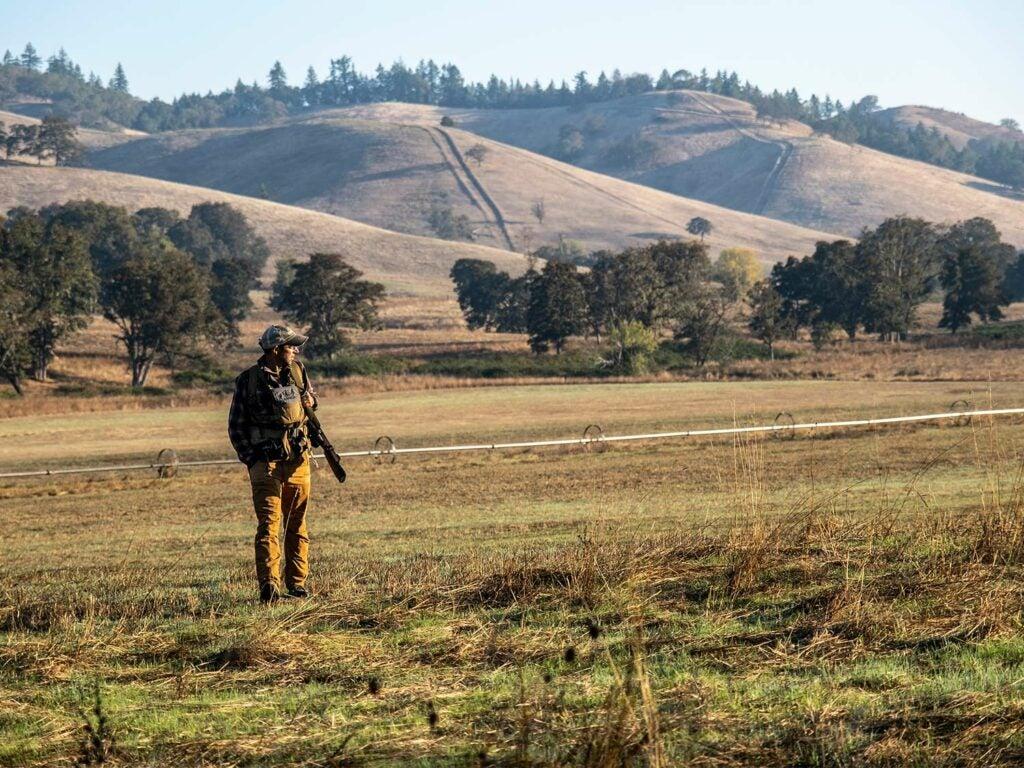 A hunter walks through a large open field.