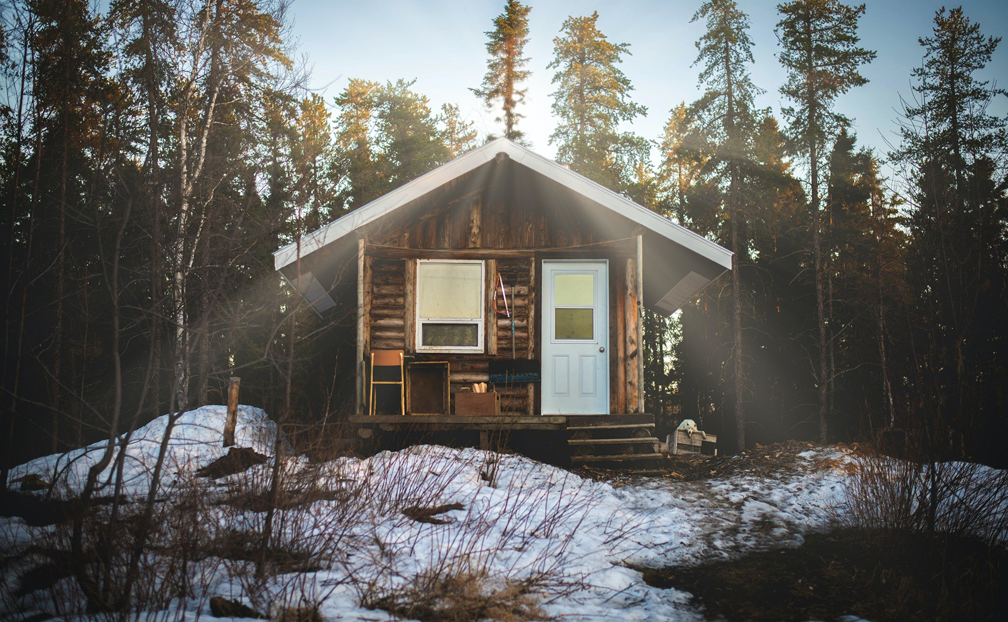 cabin in the woods with sun shining over the roof and snow on the ground