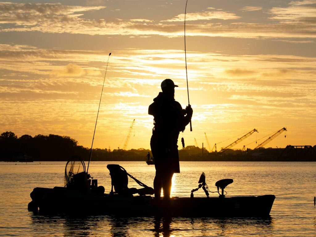 An angler fishing off of a kayak against the sunset.