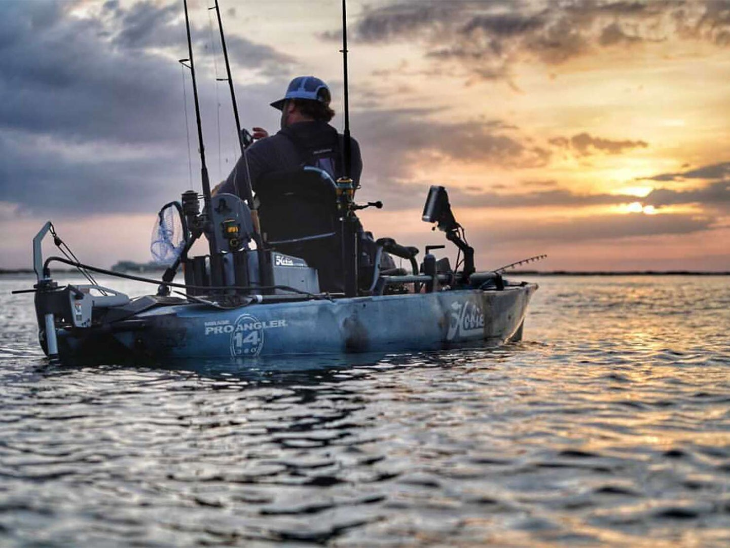 An angler sits on a kayak and fishes.