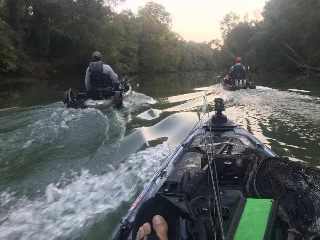 A group of anglers in a kayak troll through a stream.