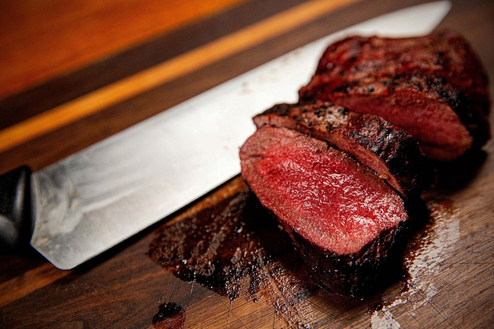 A perfectly cooked medium-rare venison steak on a cutting board.