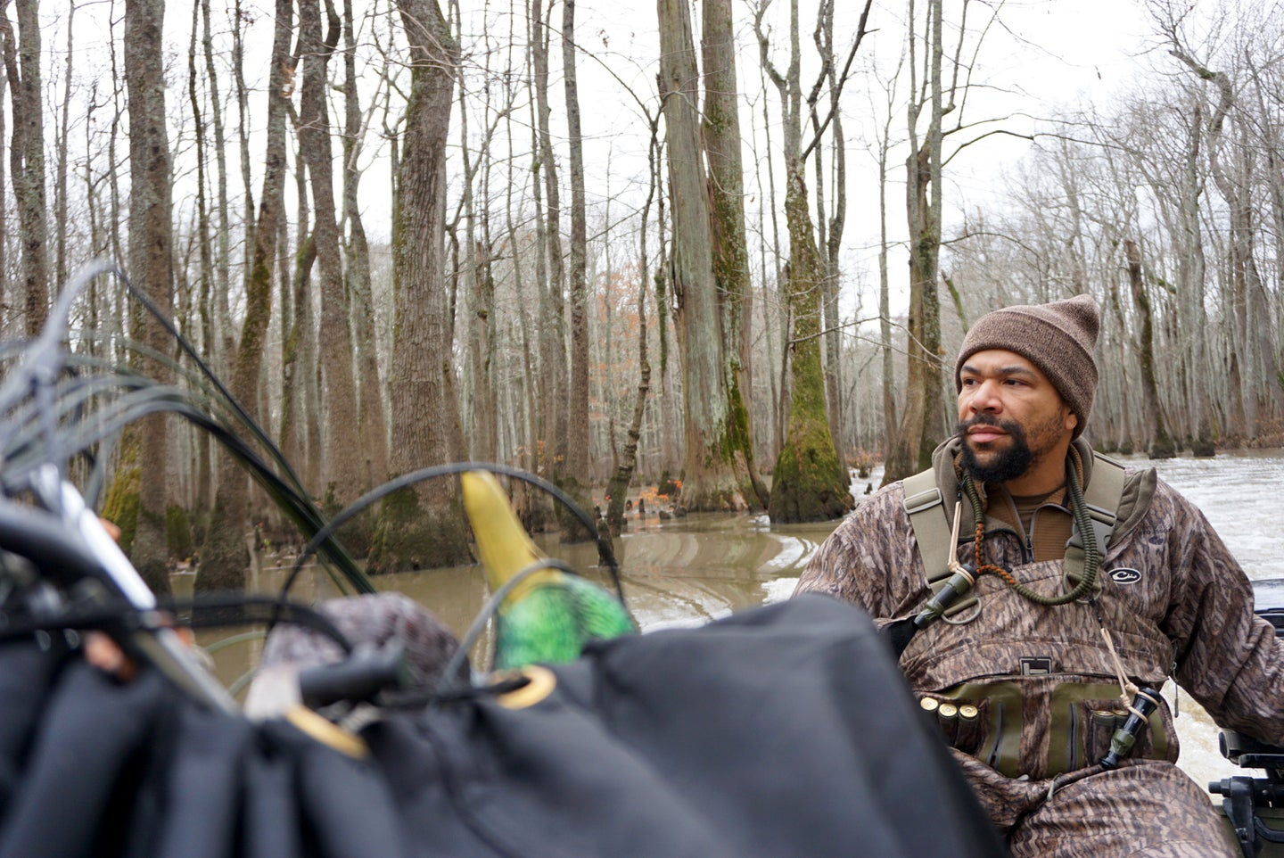 A duck hunter steers a boat loaded with decoys through flooded timber.