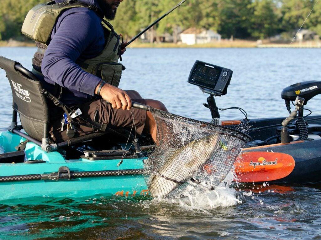 An angler pulls a fish into a kayak using a net.
