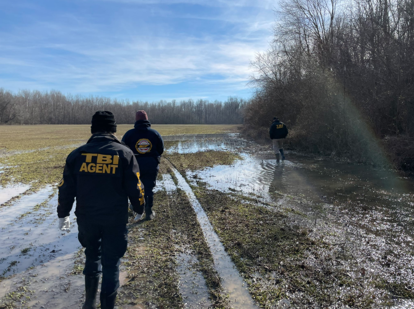 Three men in navy TBI Agent uniforms search a muddy wet field for David Vowell.