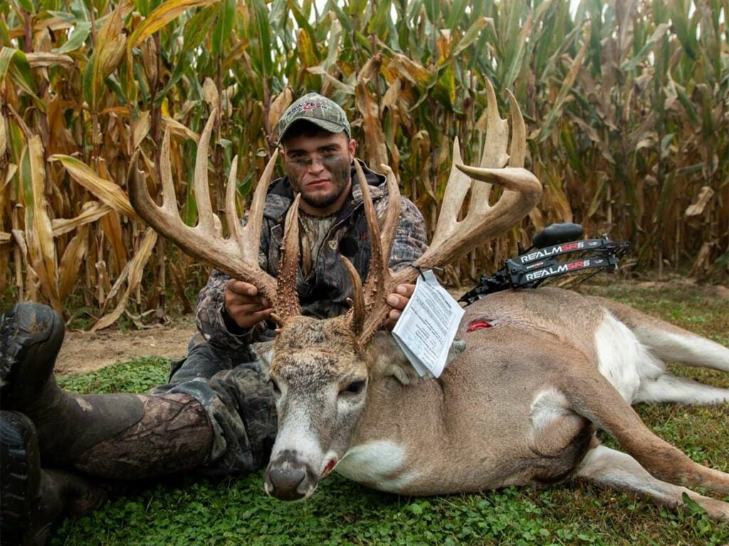 A bow hunter sits behind a big Ohio buck and holds its head by the antlers.