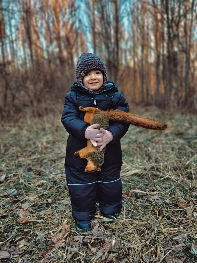 A young kid in a snow suit holds a fox squirrel and smiles.