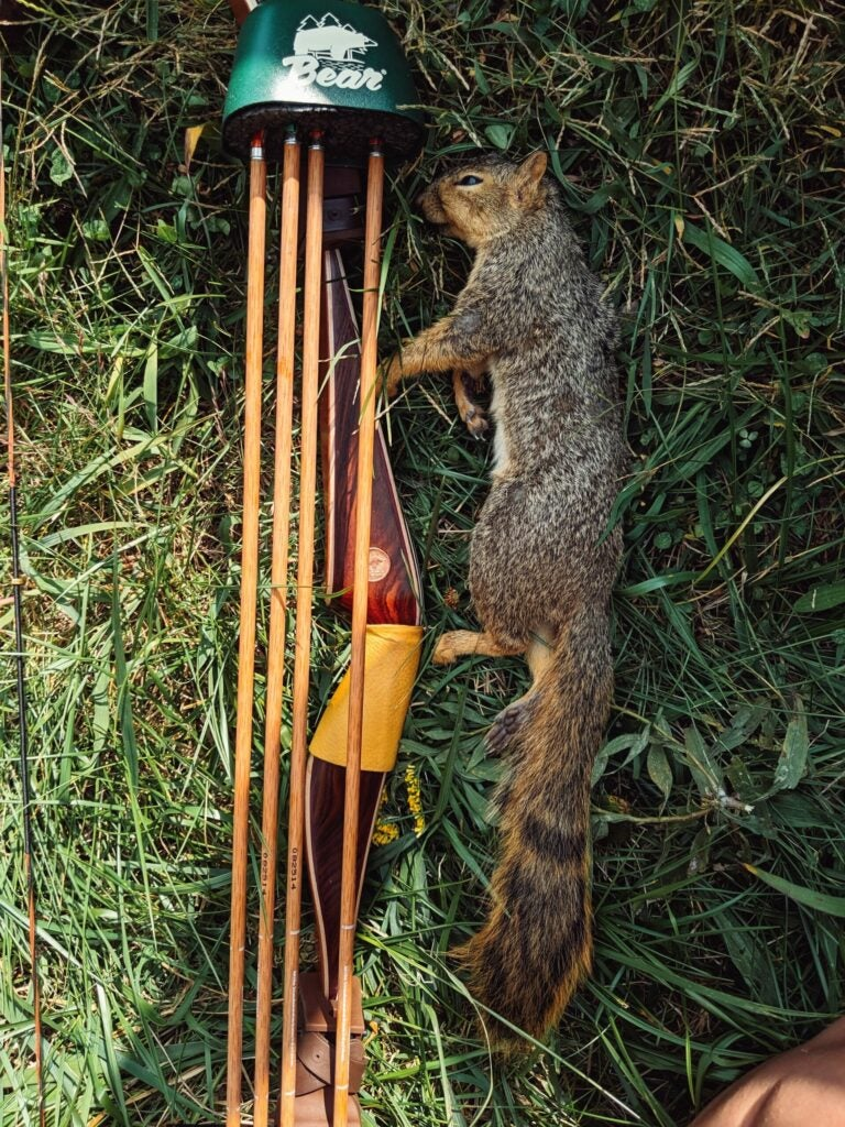 A dead squirrel beside a traditional bow and quiver.