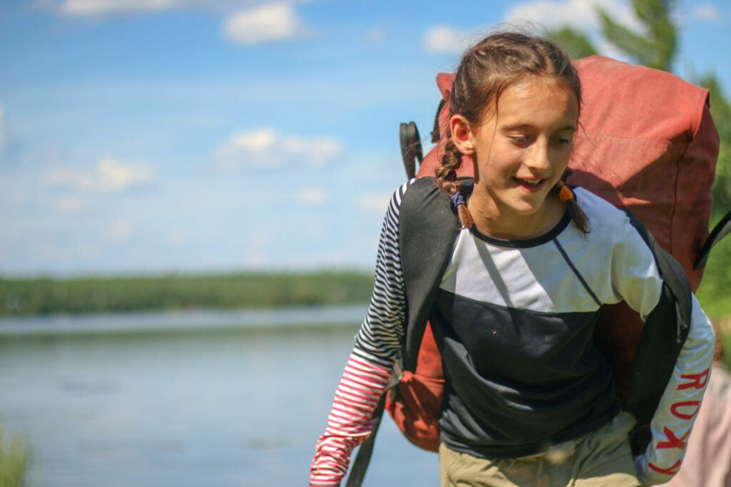 A girl shoulders her pack on the shore of a northern lake.