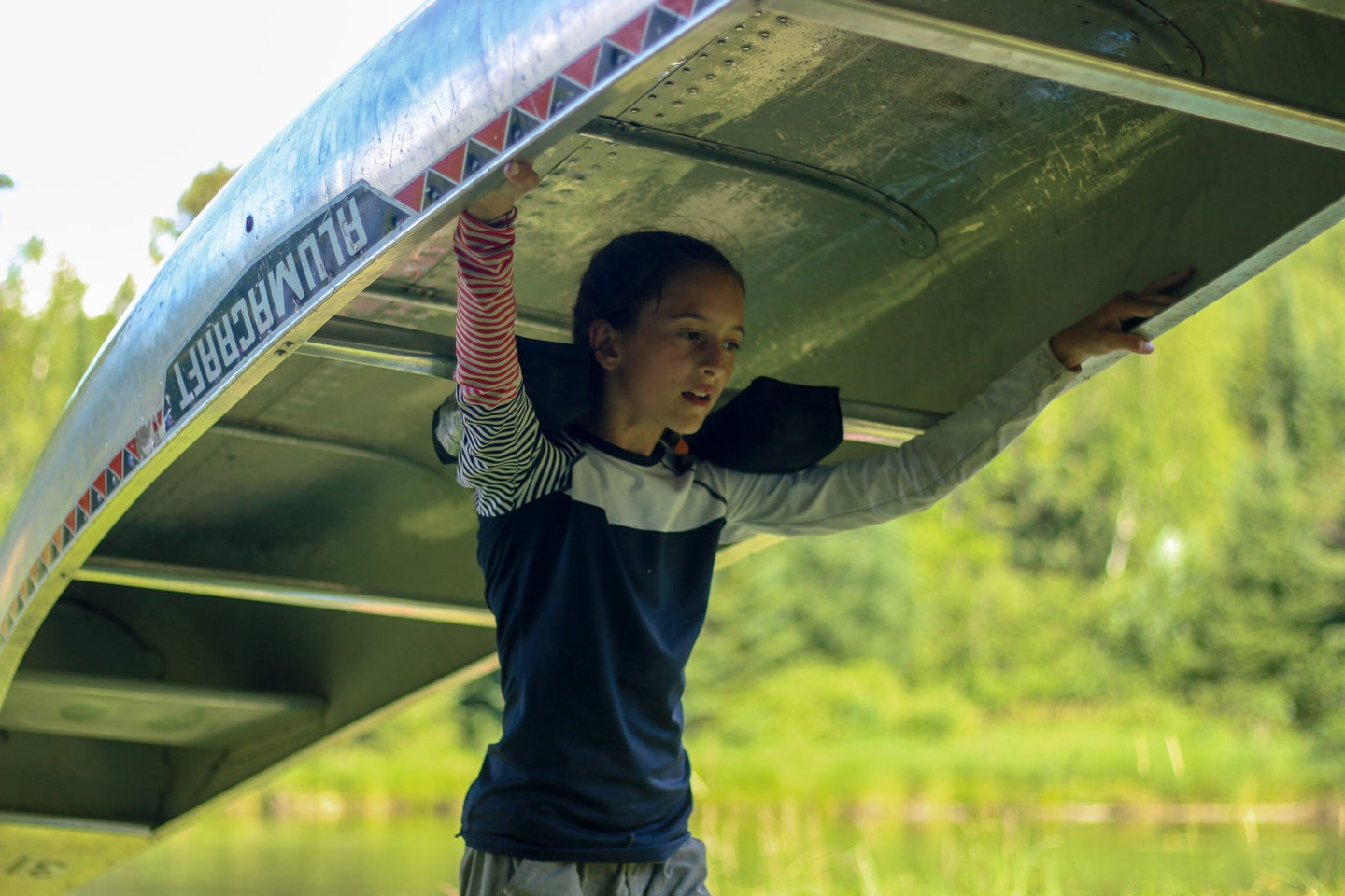 A girl carries an aluminum canoe on her shoulders during a portage.