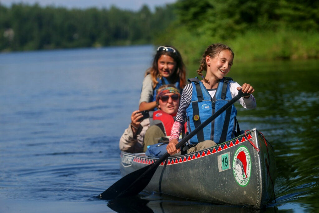 Two girls paddle a canoe on a northern like while a counselor sits in the middle of the boat.