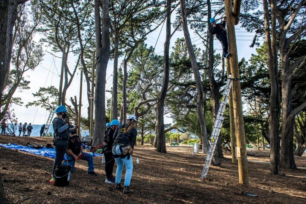 A group of students in helmets and harnesses waits their turn to climb a ropes course.