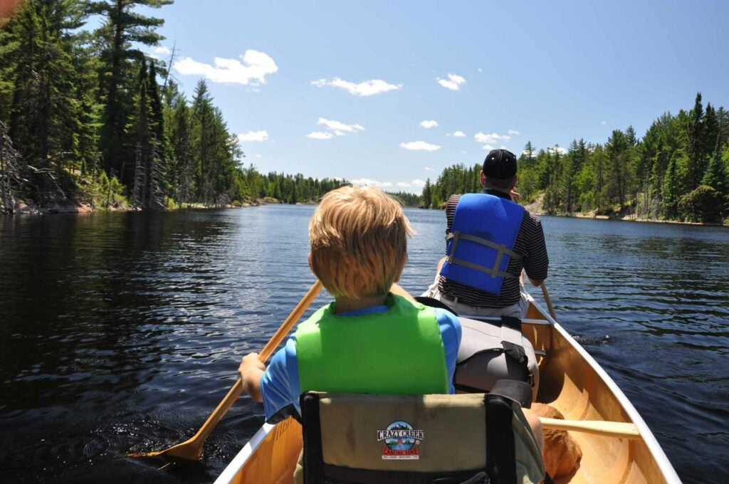 A kid and an adult paddle a canoe while social distancing in the Boundary Waters Canoe Area Wilderness.