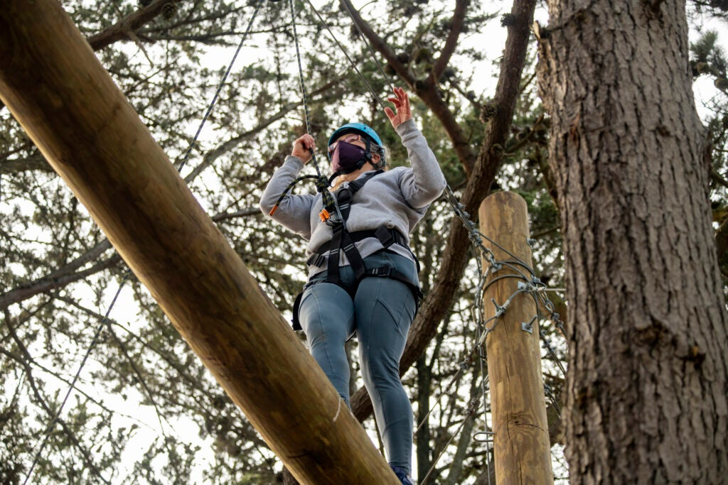 A girl balances on a log in a ropes course in the San Francisco Bay Area.