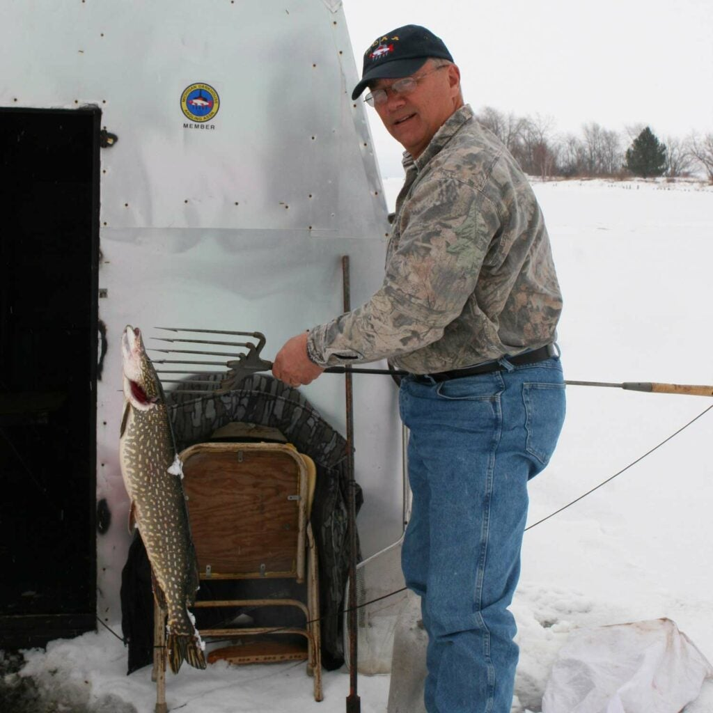 A man stands next to a large shed and an ice fishing hole.