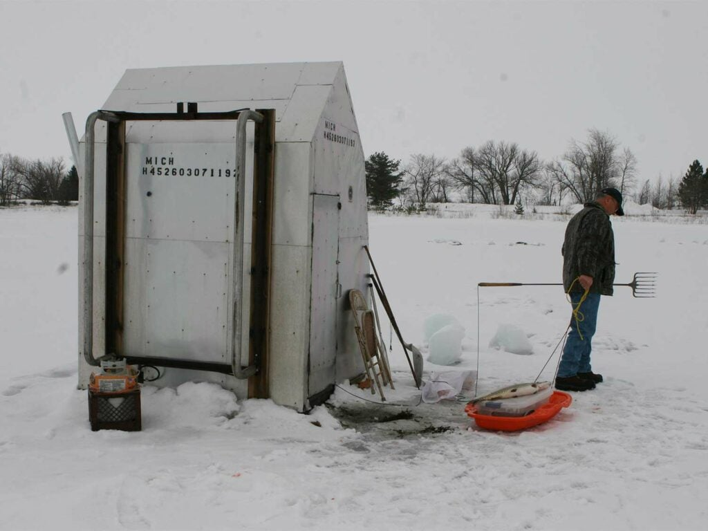 A man stands in the snow next to a shed.