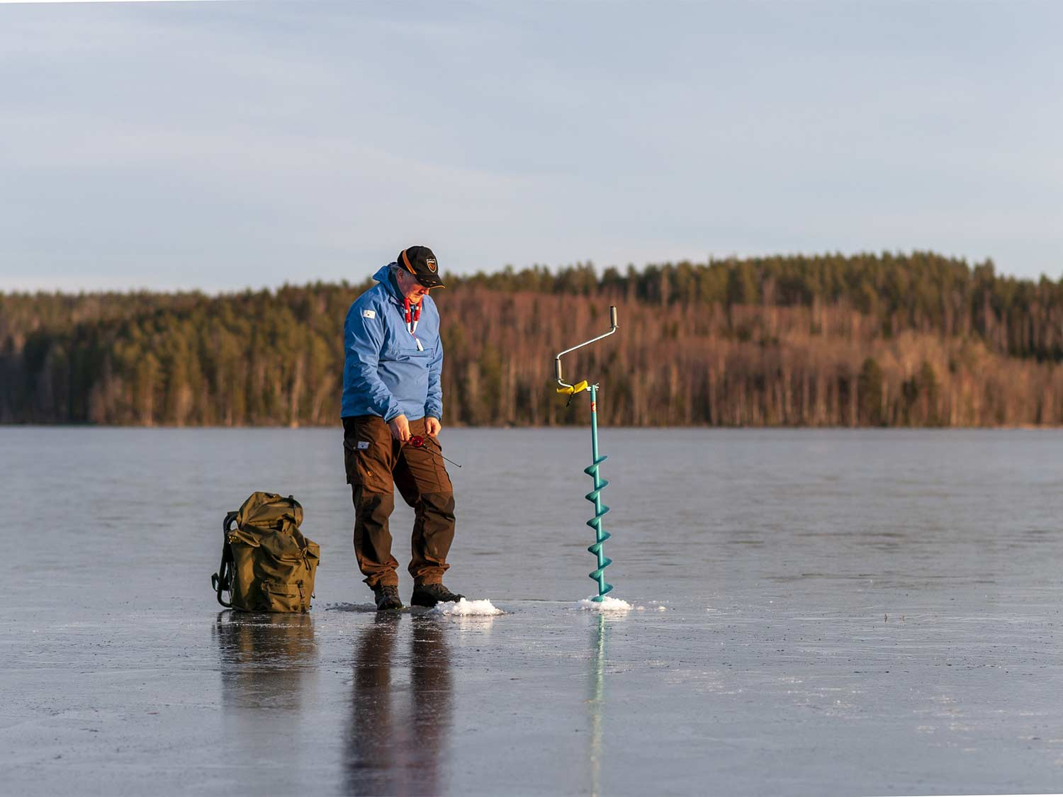 A man walks on a frozen lake, using an auger to drill a hole into the ice.