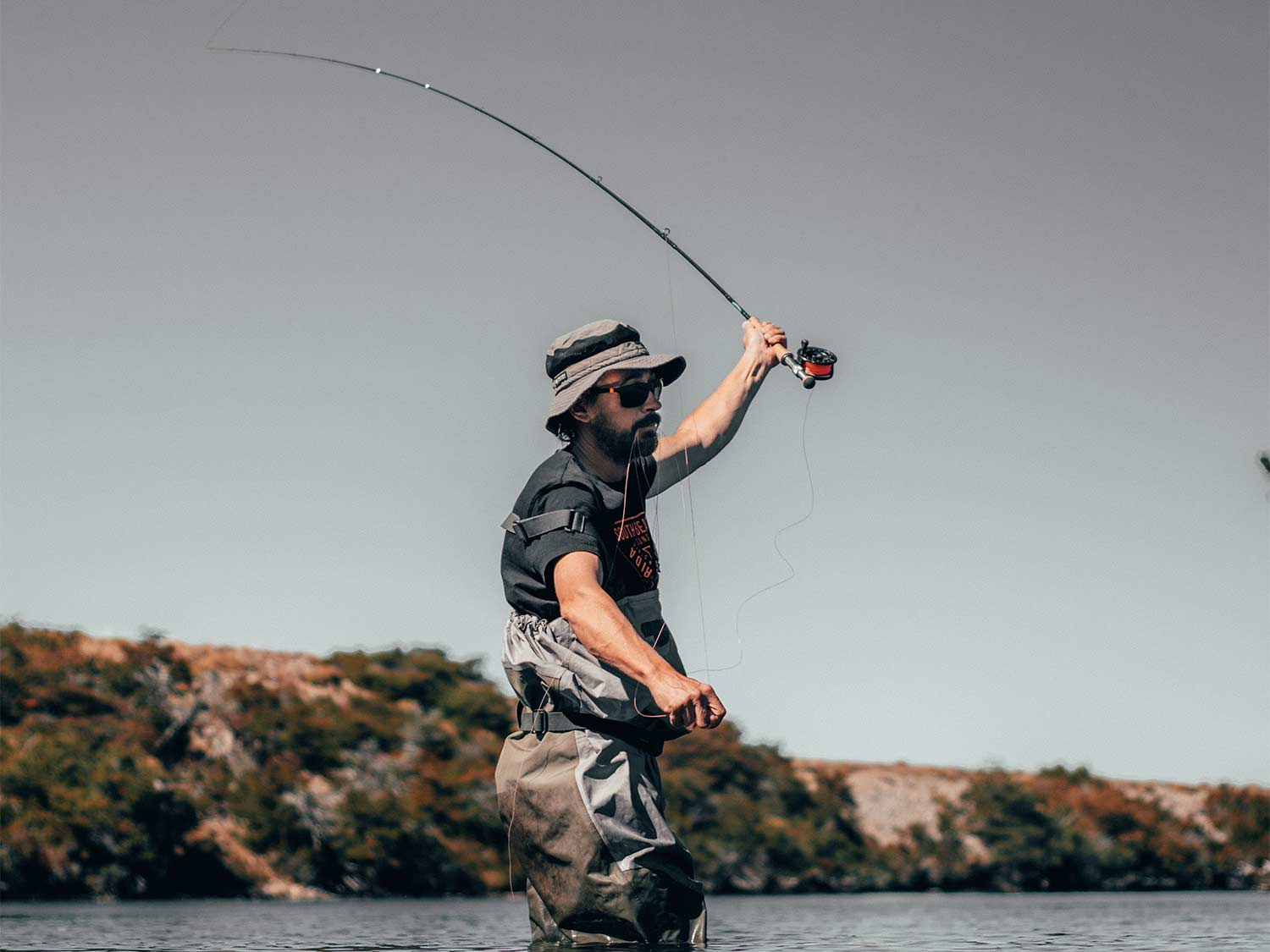 A fisherman wading into the waters while casting a fishing reel.