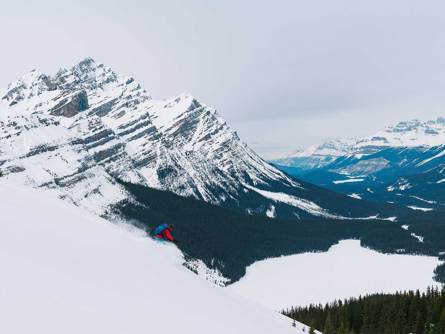 A person in the best backcountry skis, skis down a snowy mountain.