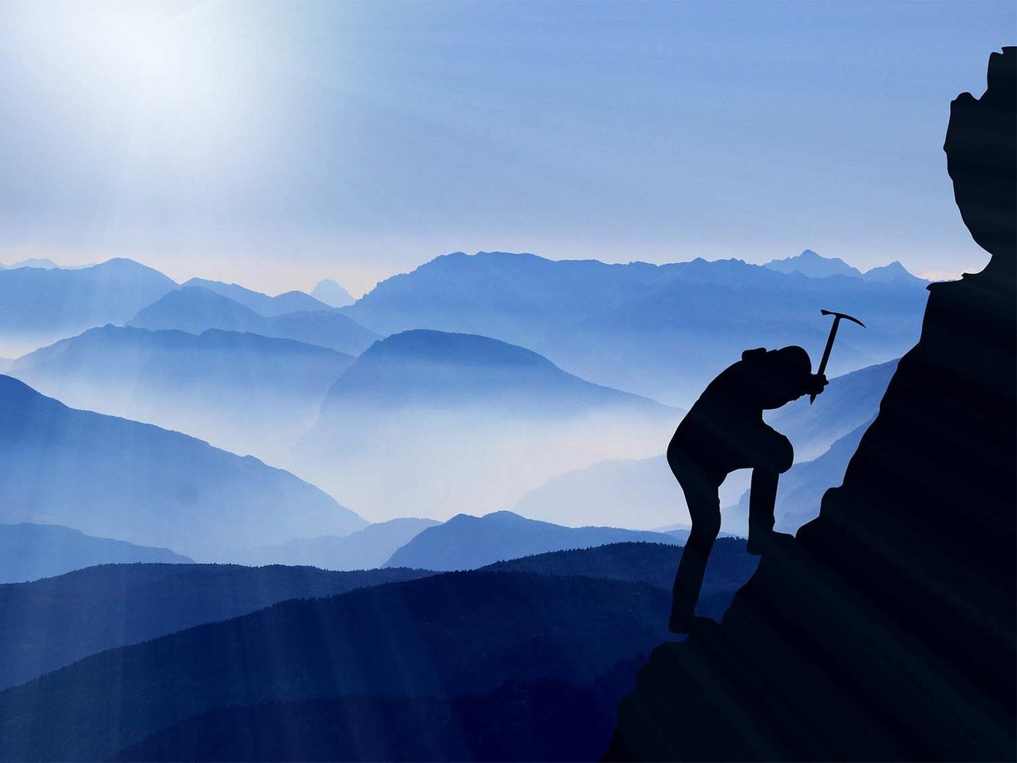 A person climbs a mountainside using an ice pick.