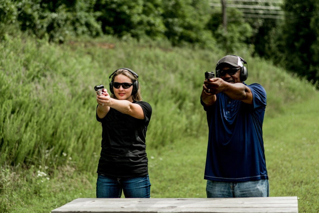 A white woman and a Black man holding handguns stand behind a table at an outdoor shooting range.