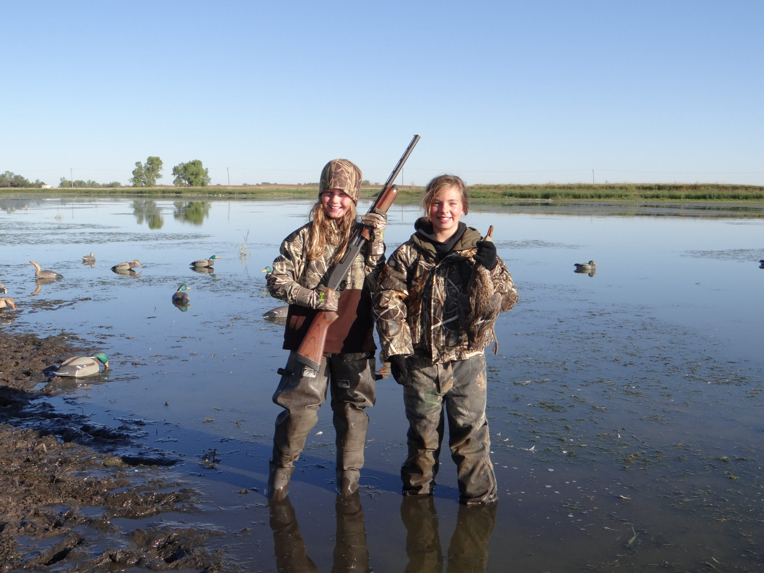 A pair of youth waterfowl hunters hold up a shotgun and a duck.