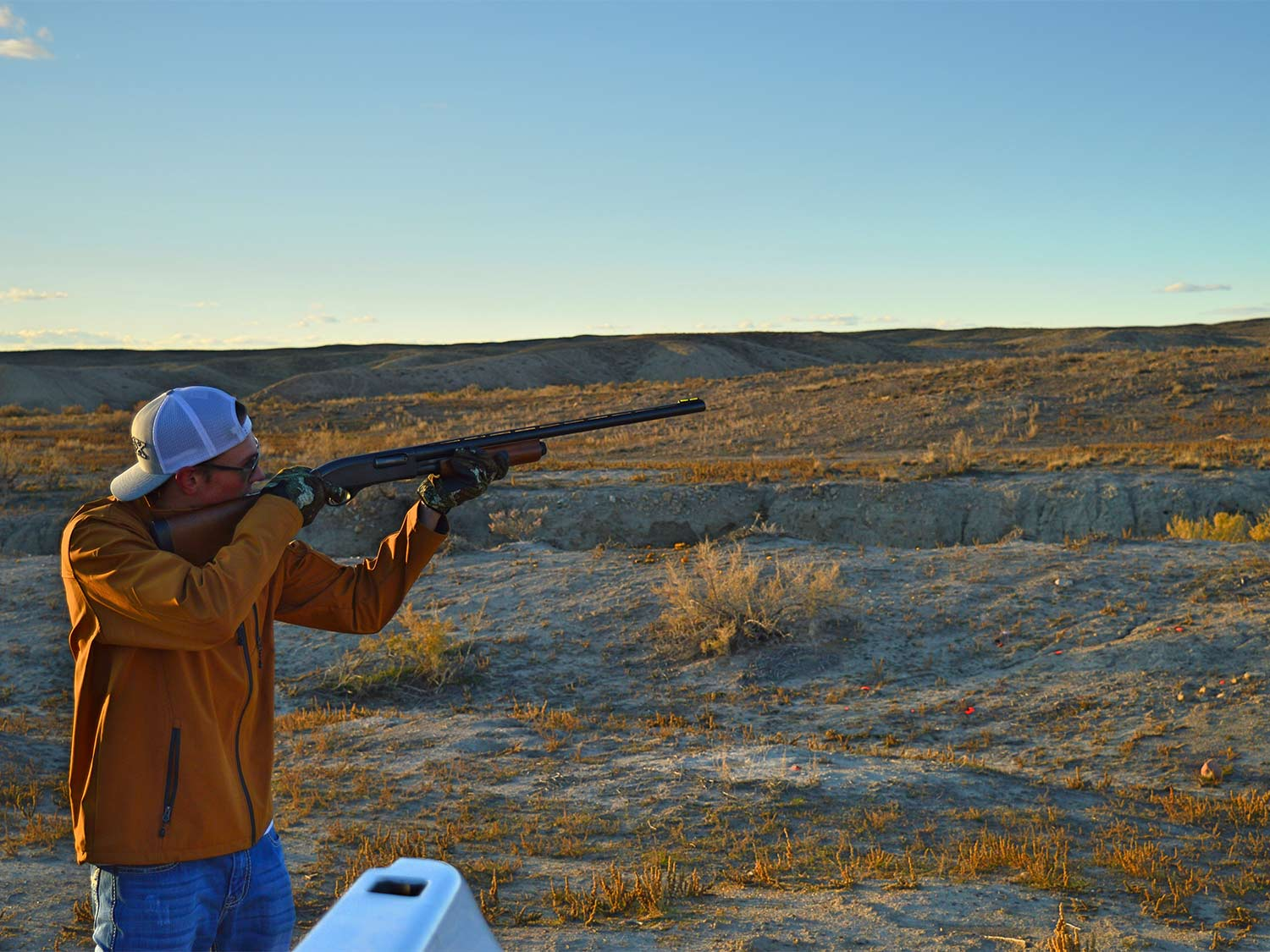 A man aims a shotgun in a large open field wearing the best shooting gloves.