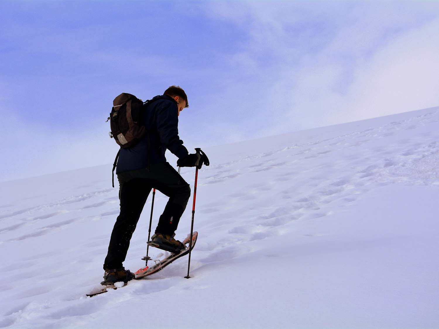 A hiker walks up a hill of snow wearing the best snowshoes.