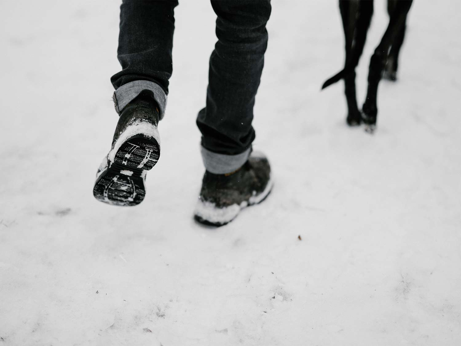 A man walks through the snow with a dog, wearing the best winter boots for men
