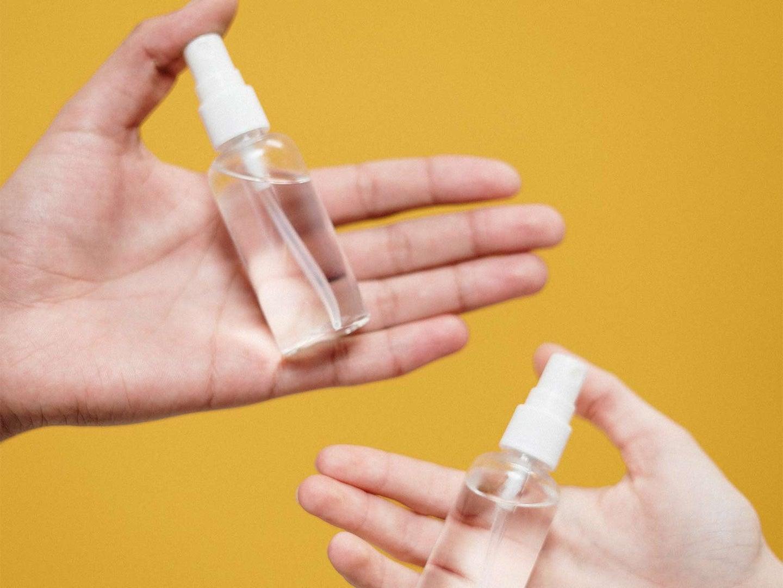 Two hands holding spray bottles.