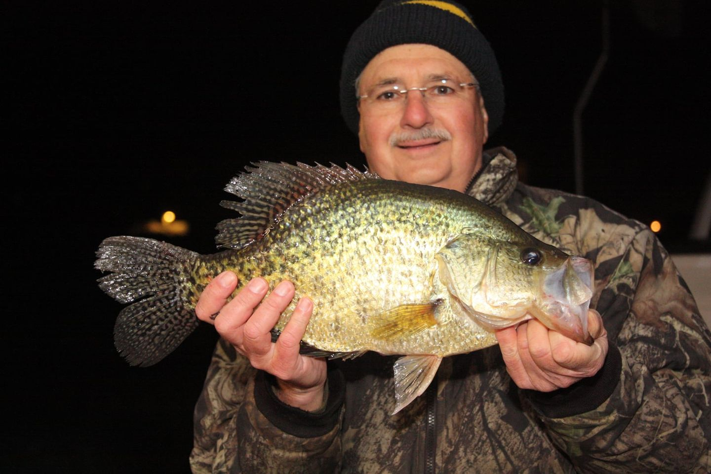 An angler holds up a large crappie.