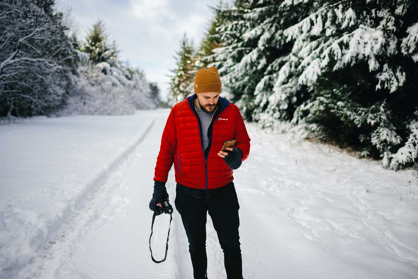 Man standing in the snow looking at his phone
