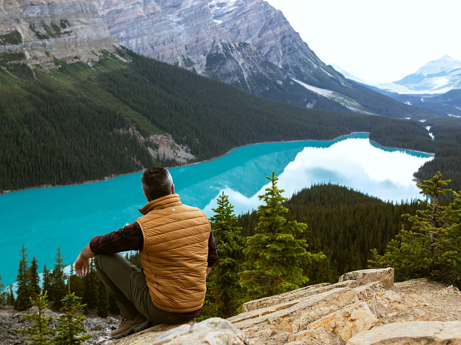 Man wearing the best heated vest, sits on a mountain side over a lake.