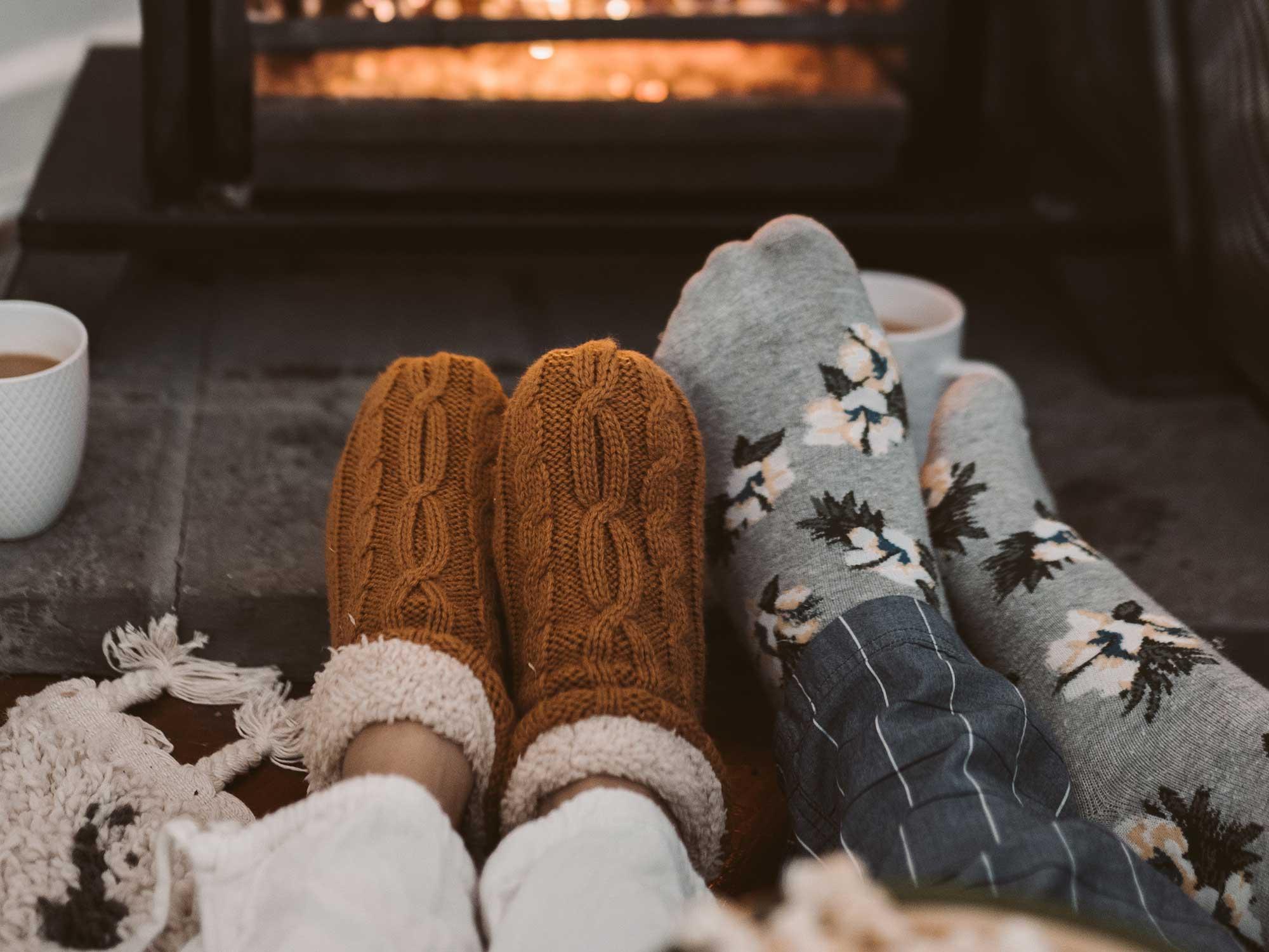 People wearing slipper socks by a fire