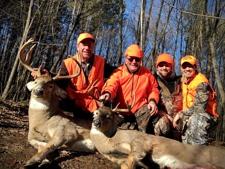 Wisconsin deer hunters in orange and camo with two mature bucks.