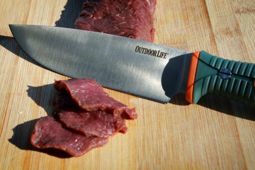 An Outdoor Life chef's knife with venison on a wooden cutting board.