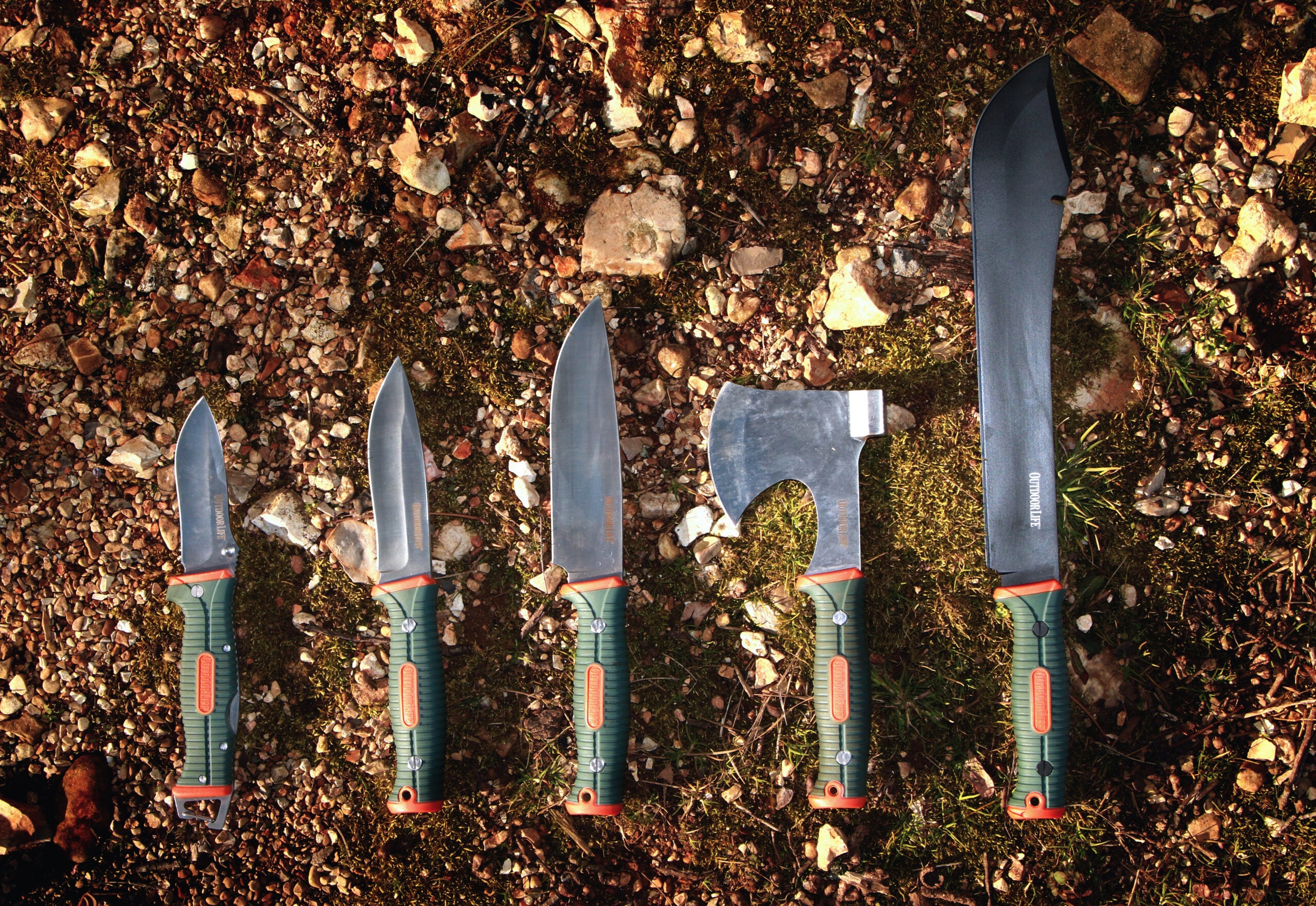 A row of Outdoor Life brand camping tools and knives, on a gravel and moss background.