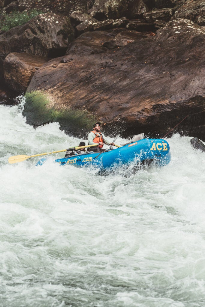 A fishing and rafting guide bombing down a rapid in an oar raft.