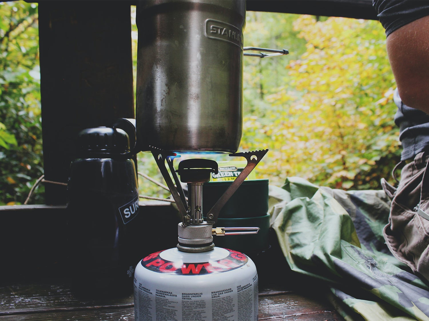 The best backpacking stove on a table next to a person.