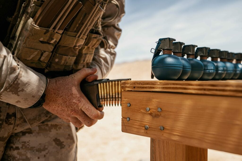 A Marine loads 5.56 rounds into a magazine before a live fire exercise.