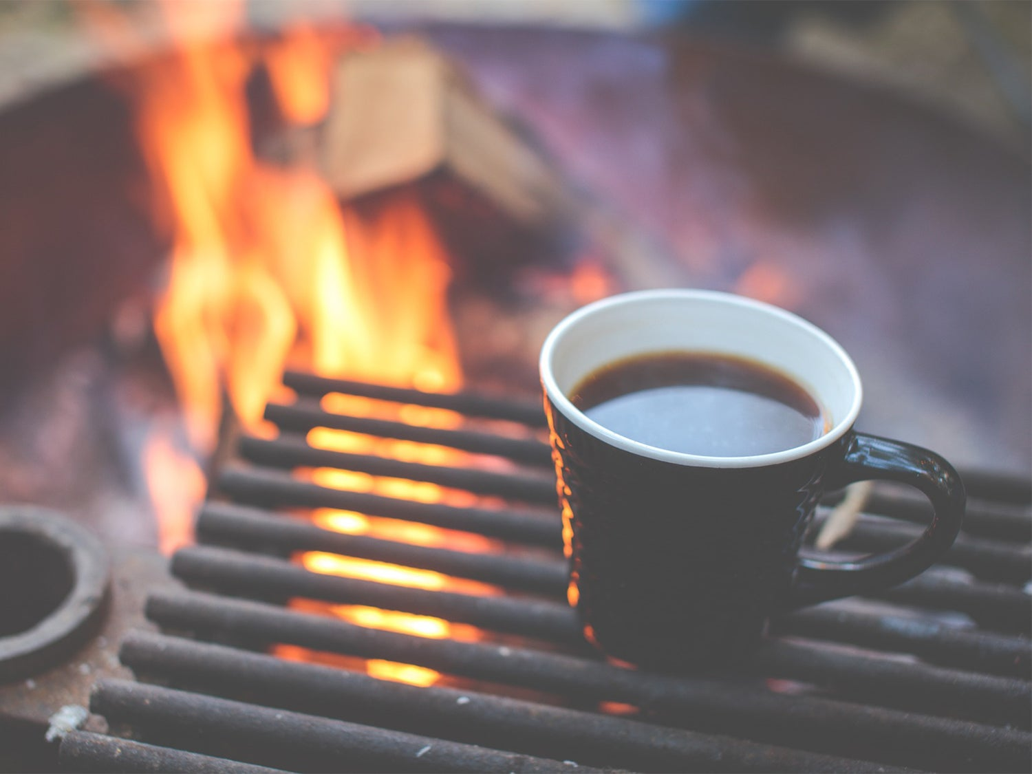 A cup of coffee beside a campfire.