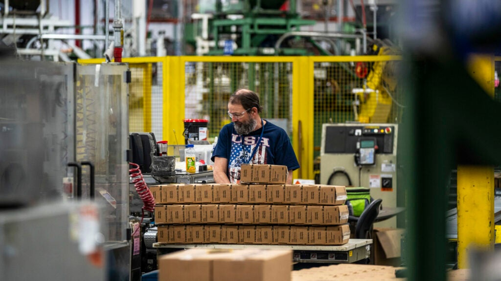 A Federal Premium factory work stacking up boxes for packing ammo.