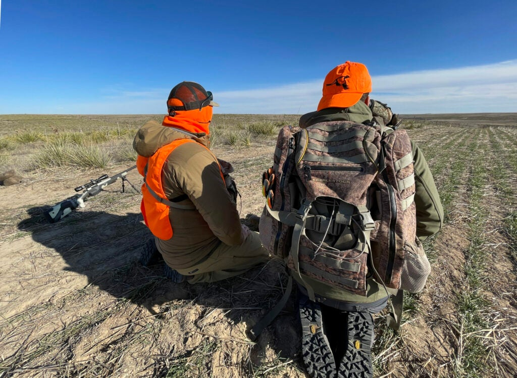 Two hunters kneel beside a rifle as they glass for deer in Eastern Colorado.
