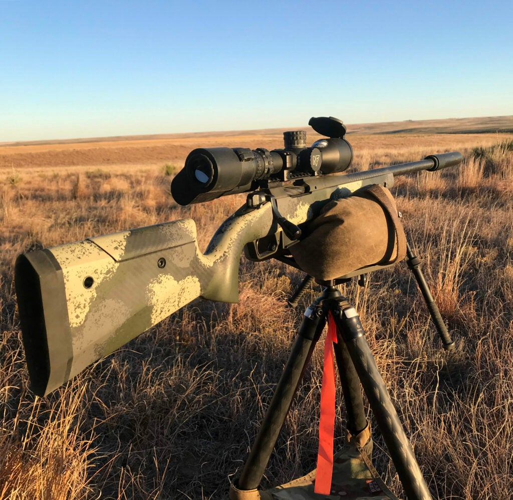 A camo-finished Springfield Waypoint 2020 hunting rifle resting on a tripod in the field.