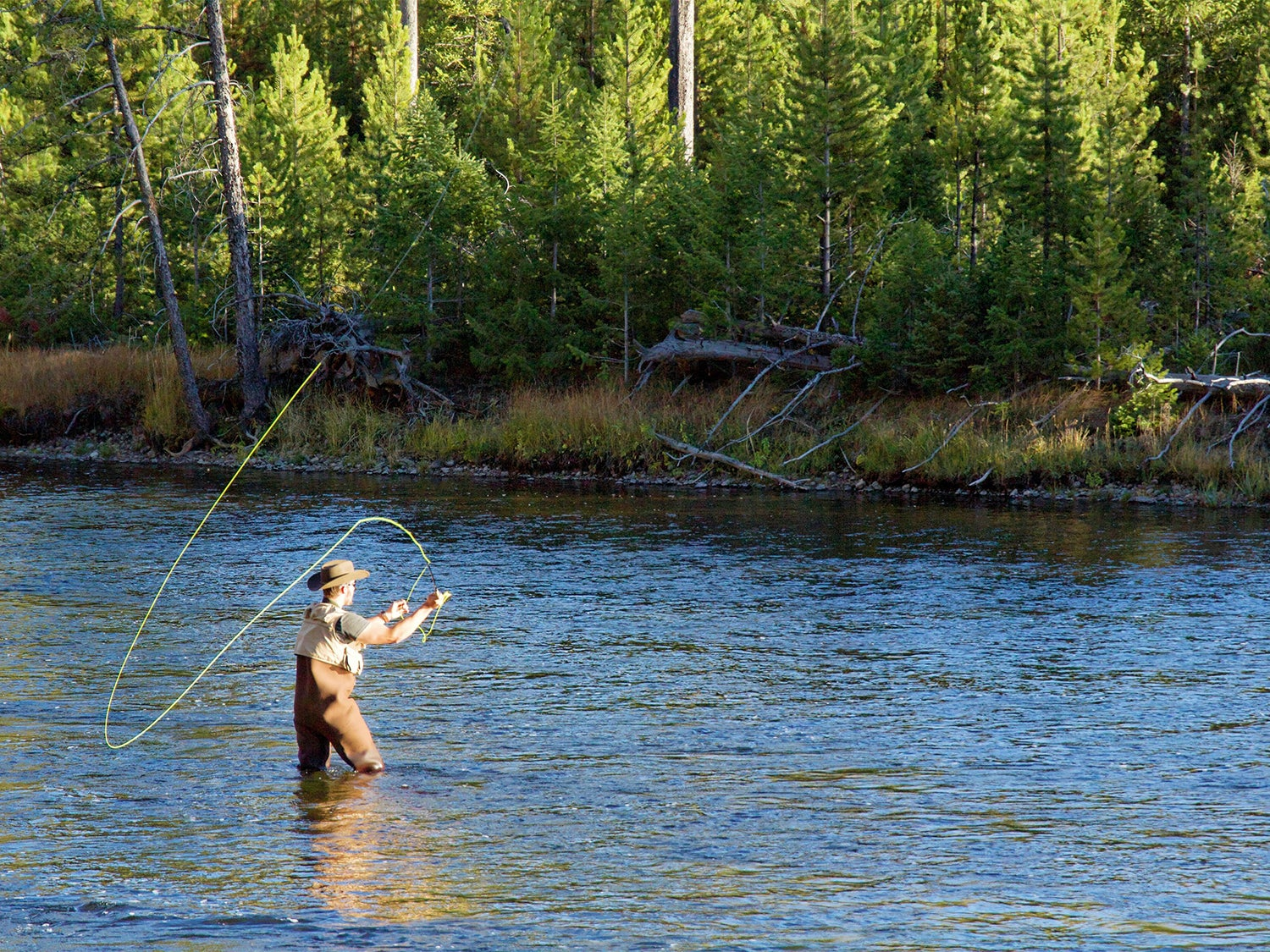 An angler wades through a river while flyfishing, wearing the best fishing vest.