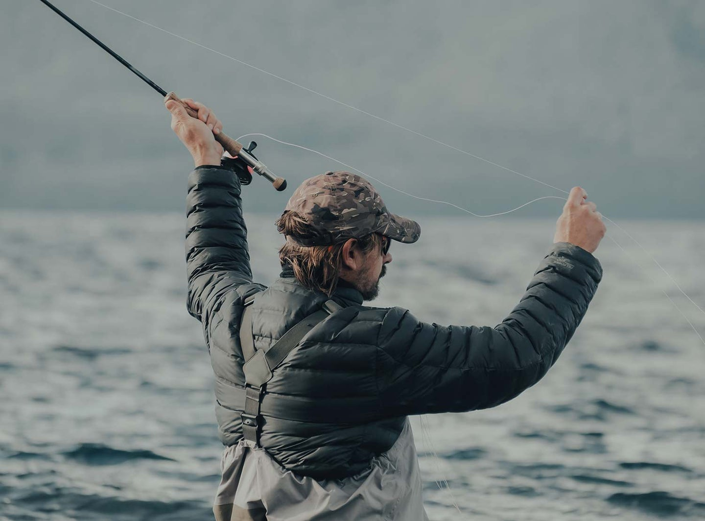 A man prepares to cast a fishing line in the water.