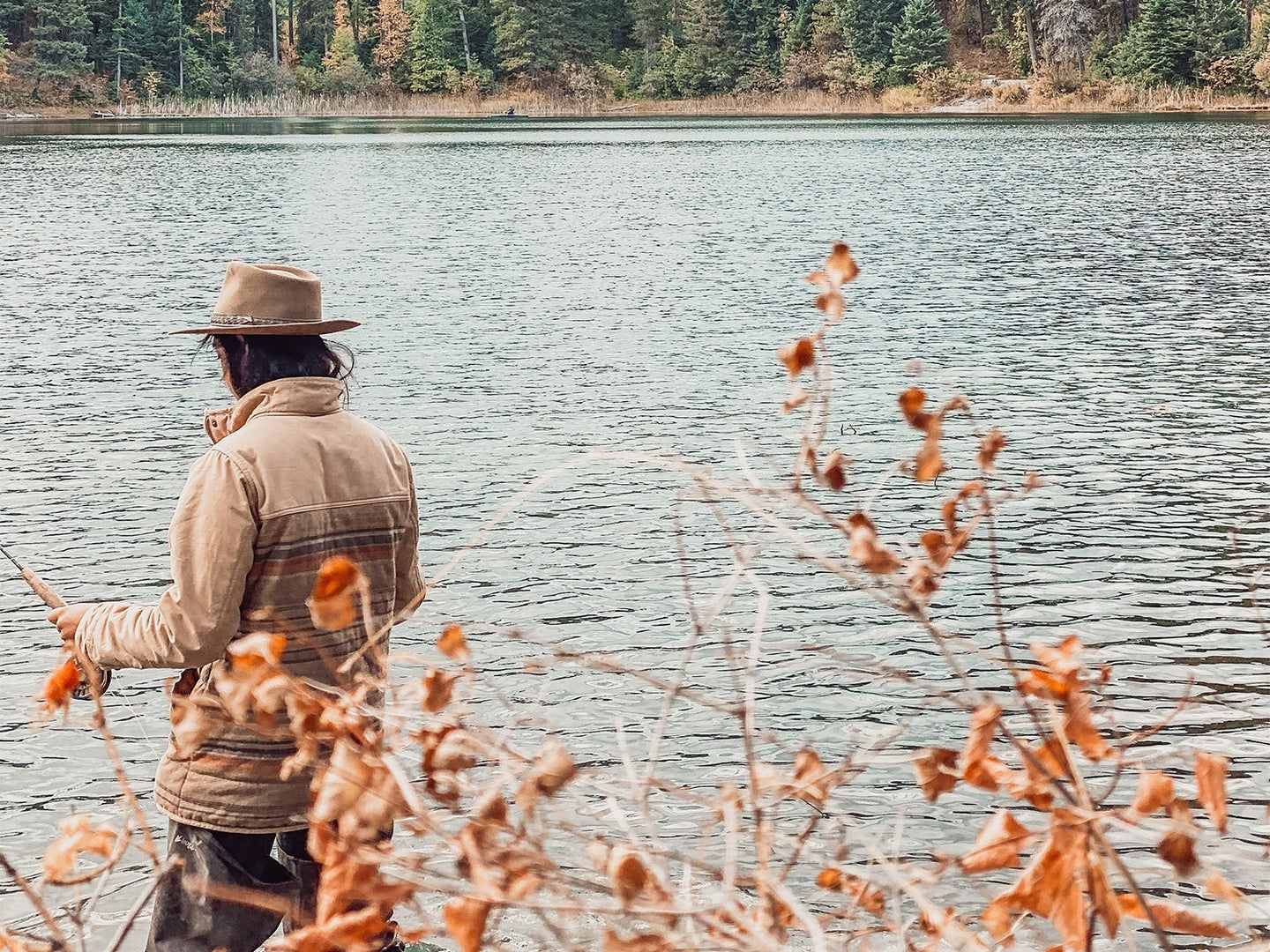 Man in brown clothing wades through a stream.