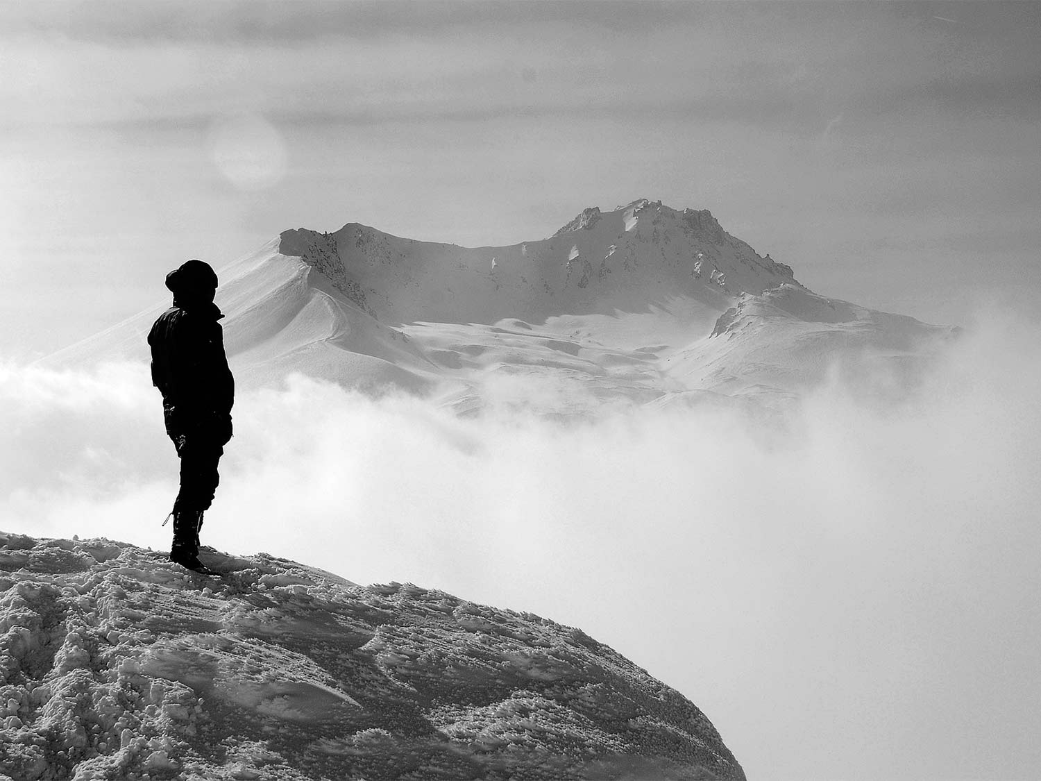 A black and white photo of a man standing on a mountainside, wearing the best soft shell jacket.