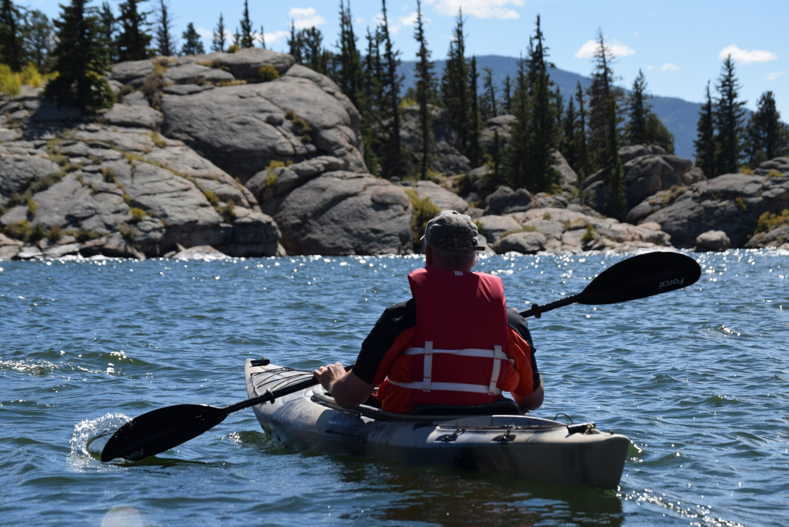 A person kayaks in the waters of the wilderness wearing the best fishing life vest.